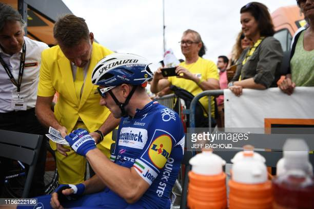 Italy's Elia Viviani picks a card to a magician performing a trick before the start of the twelfth stage of the 106th edition of the Tour de France...