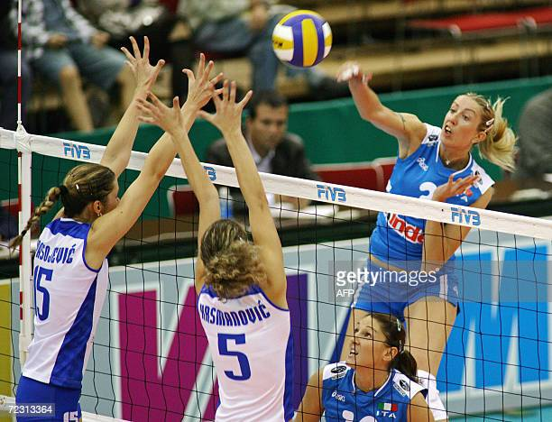 Italy's Elisa Togut spikes the ball over blocks of Serbia and Montenegro's Anja Spasojevic and Natasa Krsmanovic during the women's first round Pool...