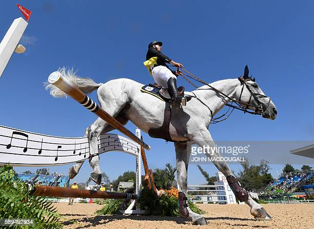 Italy's Emanuele Gaudiano on Caspar 232 crashes through an obstacle during the Equestrian's Show Jumping first qualifier event of the 2016 Rio...