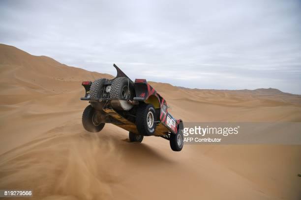 TOPSHOT Italy's Eugenio Amos and his codriver Sebastien Delaunay of France ride over sand dunes while competing during the Stage 12 of the Silk Way...