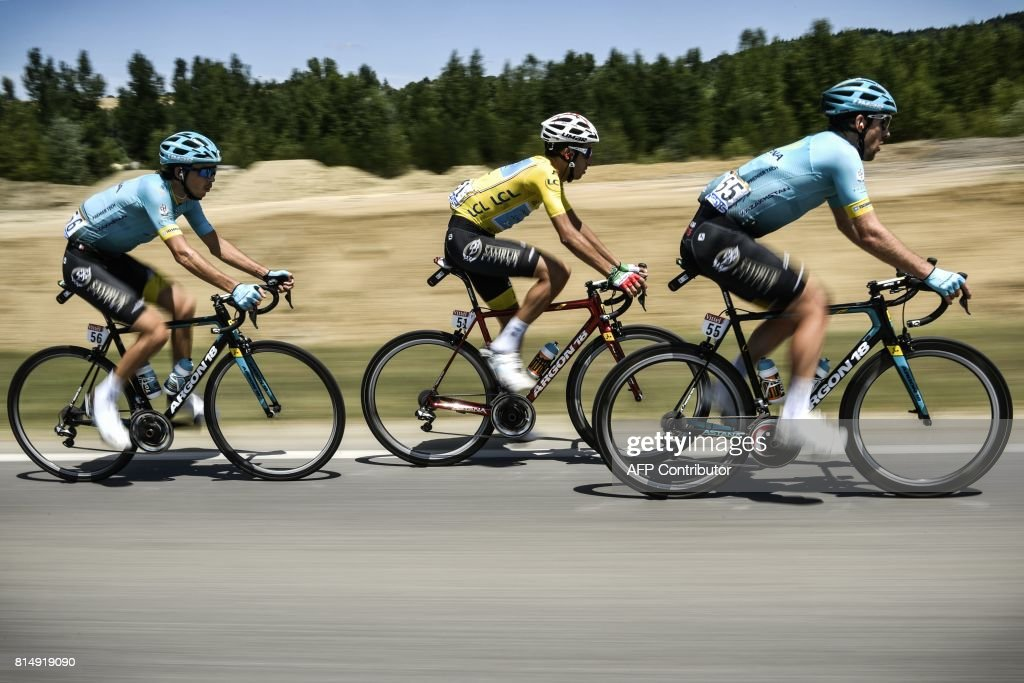 Italy's Fabio Aru (C), wearing the overall leader's yellow jersey, rides with his teammates of the Kazakhstan's Astana Pro cycling team Kazakhstan's Dmitriy Gruzdev (R) and Kazakhstan's Bakhtiyar Kozhatayev during the 181,5 km fourteenth stage of the 104th edition of the Tour de France cycling race on July 15, 2017 between Blagnac and Rodez. /