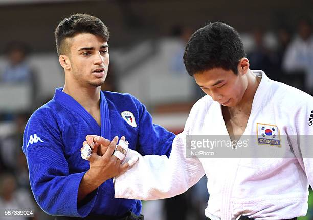 Italy's Fabio Basile holds the hand of South Korea's An Baul after the men's 66kg judo final at the Rio 2016 Olympic Games in Rio de Janeiro on Aug 7...