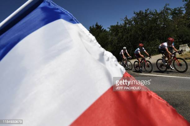 Italy's Fabio Felline and Belgium's Tim Wellens , wearing the best climber's polka dot jersey ride as a French national flag flies in foreground...