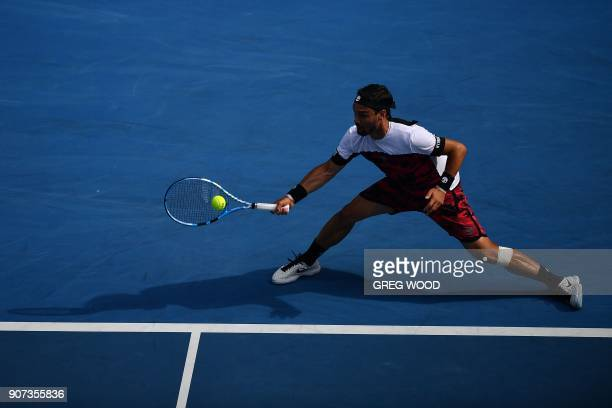 Italy's Fabio Fognini hits a return during their men's singles third round match against France's Julien Benneteau on day six of the Australian Open...
