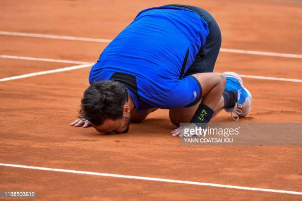 Italy's Fabio Fognini kisses the court as he celebrates after winning against Serbia's Dusan Lajovic at the end of the final tennis match of the...