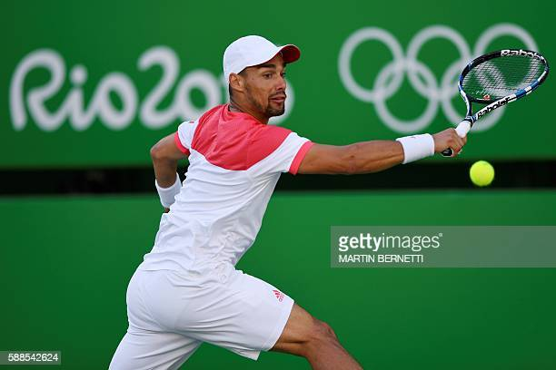 Italy's Fabio Fognini returns the ball to Britain's Andy Murray during their men's singles third round tennis match at the Olympic Tennis Centre of...