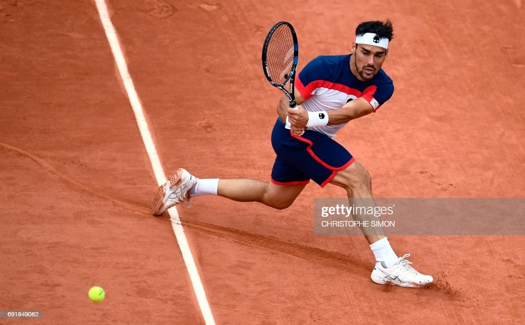 Italy's Fabio Fognini returns the ball to Switzerland's Stanislas Wawrinka during their tennis match at the Roland Garros 2017 French Open on June 3, 2017 in Paris. /