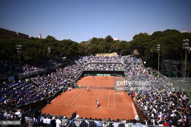 Italy's Fabio Fognini serves as playing with Italy's Simone Bolelli against France's Nicolas Mahut and France's PierreHugues Herbert during the Davis...