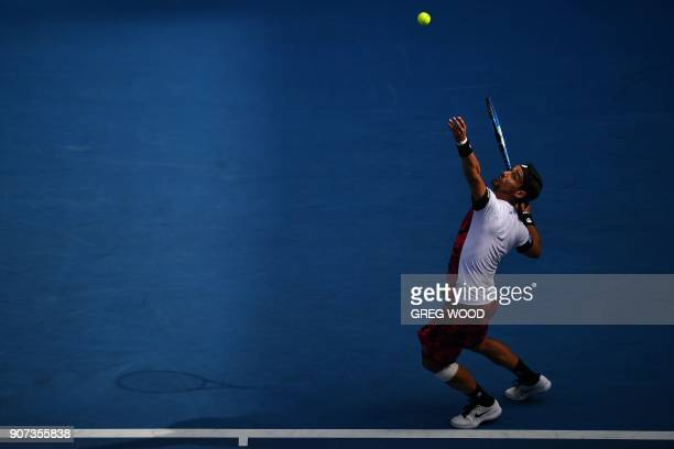 Italy's Fabio Fognini serves during their men's singles third round match against France's Julien Benneteau on day six of the Australian Open tennis...