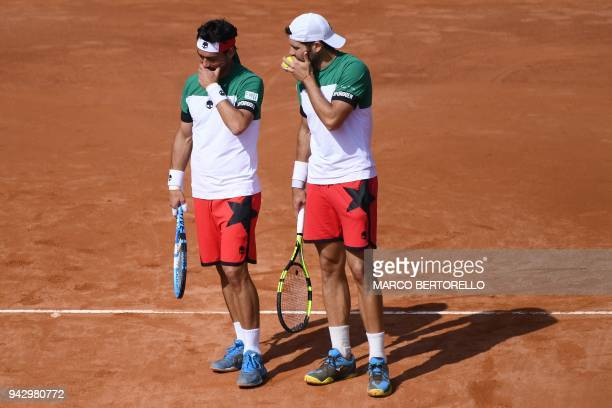 Italy's Fabio Fognini speaks with Italy's Simone Bolelli during the Davis Cup quarterfinal doubles tennis match against France's Nicolas Mahut and...