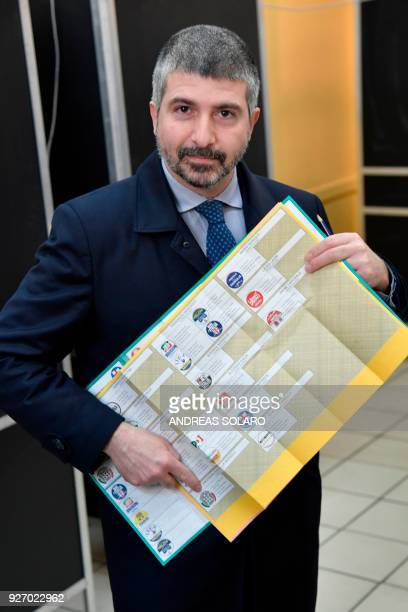 Italy's far right movement turned political party CasaPound's vice-president Simone Di Stefano shows his logo on the electoral list before to vote on...