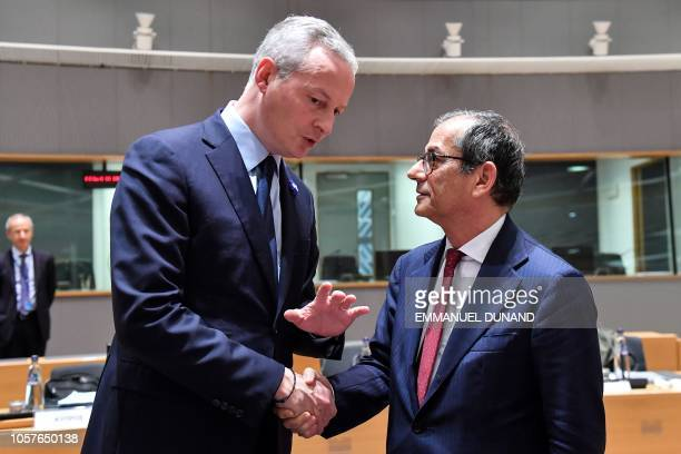 Italy's Finance Minister Giovanni Tria shakes hands with France's Finance Minister Bruno Le Maire as they attend an Eurogroup Finance ministers...