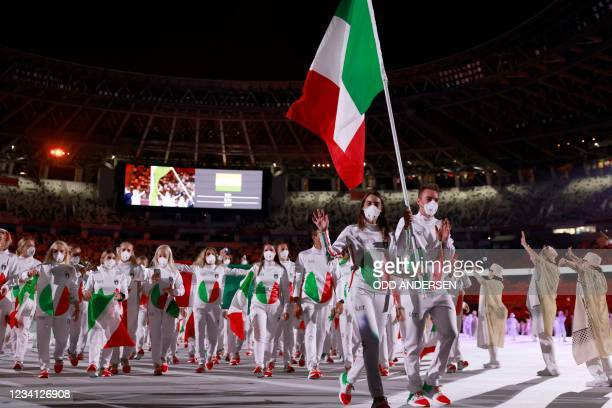 Italy's flag bearers Elia Viviani and Italy's Jessica Rossi lead their delegation as they parade during the opening ceremony of the Tokyo 2020...