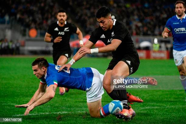 Italy's fly half Edoardo Padovani stumbles next to New Zealand's All Blacks inside centre Anton LienertBrown during the international rugby union...