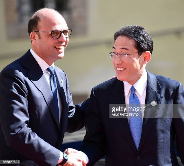 Italy's Foreign Minister Angelino Alfano shakes hands with Japanese Foreign Minister Fumio Kishida during a meeting of Foreign Affairs Ministers from...