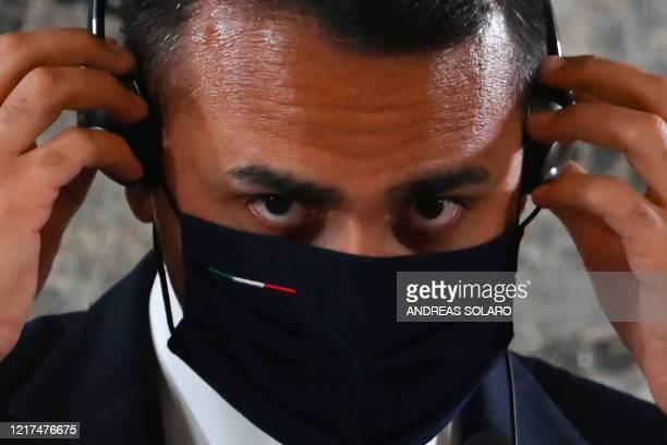 Italy's Foreign Minister Luigi Di Maio adjusts his face mask during a joint press conference with his French counterpart following their meeting on...