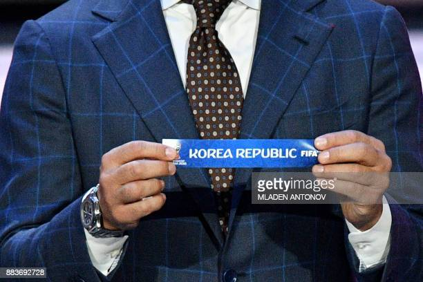 Italy's former defender and Guangzhou Evergrande's coach Fabio Cannavaro displays the slip of South Korea during the Final Draw for the 2018 FIFA...