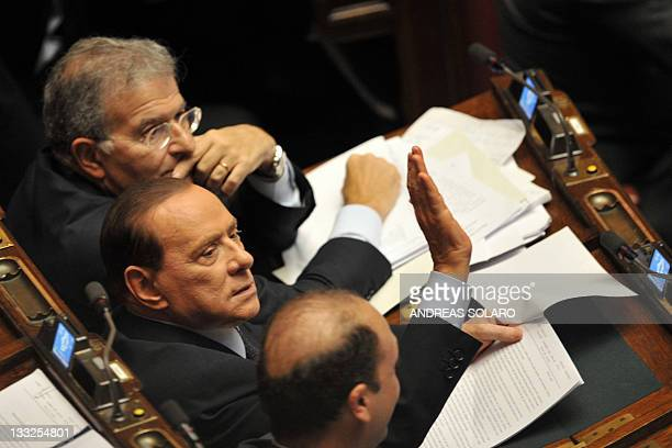 Italy's former Prime minister and head of the Popola della liberta party's delegation at the lowerhouse Silvio Berlusconi reacts during a session at...