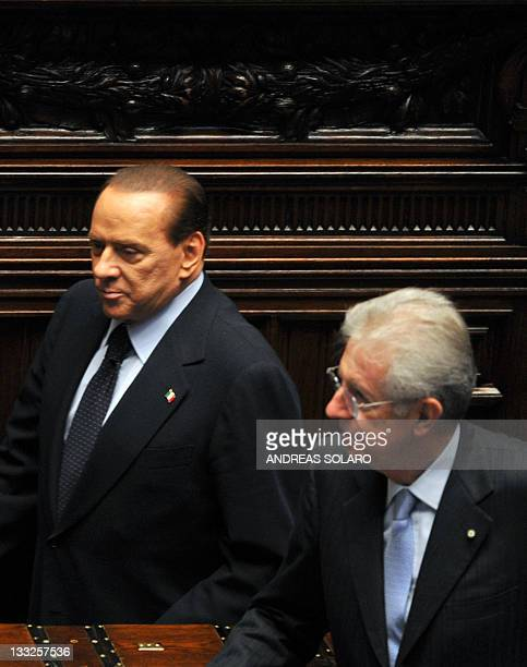 Italy's former Prime minister and head of the Popola della liberta party's group at the lowerhouse Silvio Berlusconi walks past Prime Minister Mario...