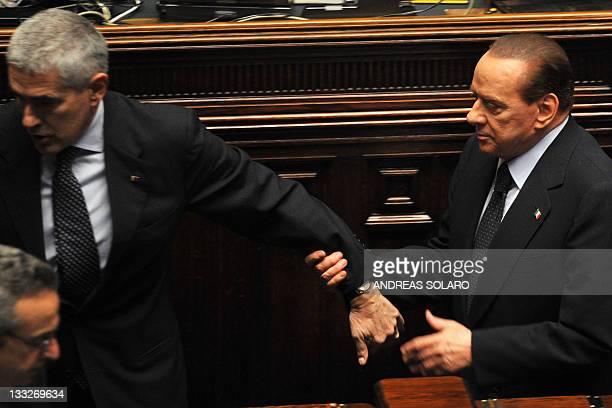 Italy's former Prime minister and head of the Popola della liberta party's delegation at the lowerhouse Silvio Berlusconi holds the arm of UDC...
