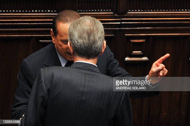 Italy's former Prime minister and head of the Popola della liberta party's group at the lowerhouse Silvio Berlusconi speaks to Prime Minister Mario...