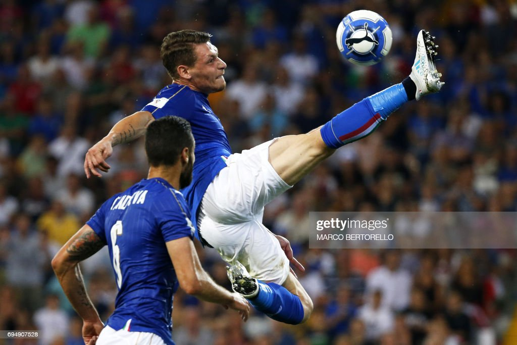 TOPSHOT - Italy's forward Andrea Belotti (C) is watched by teammate Antonio Candreva as he leaps for the ball during the FIFA WC 2018 football qualification match between Italy and Liechtenstein at The Dacia Arena Stadium in Udine on June 11, 2017. / AFP PHOTO / Marco BERTORELLO