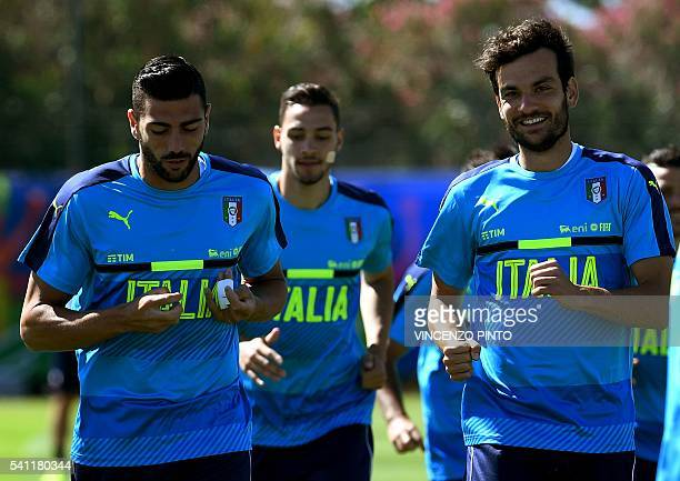 Italy's forward Graziano Pelle runs with Italy's midfielder Marco Parolo are pictured during a team training session at their training ground in...