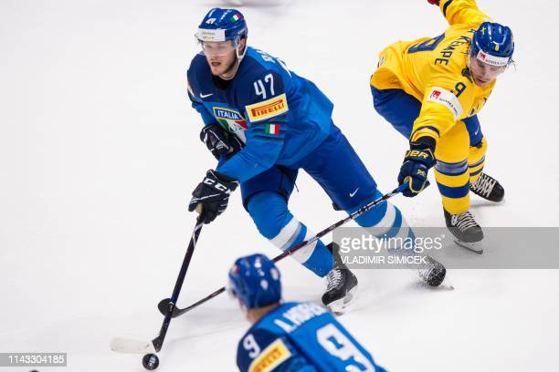 Italy's forward Joachim Ramoser and Sweden's forward Adrian Kempe vie for the puck during the IIHF Men's Ice Hockey World Championships Group B match...