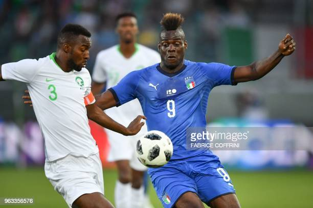 Italy's forward Mario Balotelli anfd Saudi Arabia's defender Osama Hawsawi vie for the ball during the friendly football match between Italy and...