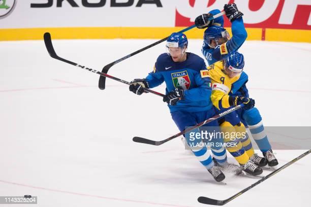 Italys forward Markus Gander Swedens forward Adrian Kempe and Italys defender Alex Trivellato vie during the IIHF Men's Ice Hockey World...