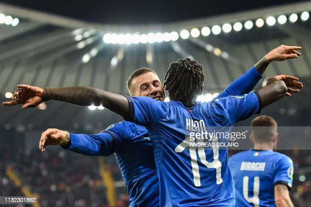 Italy's forward Moise Kean celebrates with Italy's midfielder Federico Bernardeschi after scoring during the Euro 2020 Group J qualifying football...
