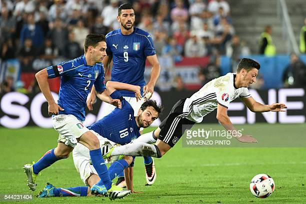 TOPSHOT Italy's forward Pelle defender Mattia De Sciglio and midfielder Marco Parolo vies for the ball against Germany's midfielder Mesut Oezil...