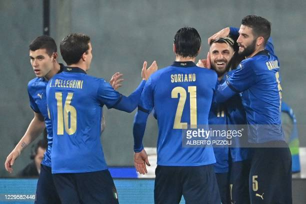 Italy's forward Vincenzo Grifo celebrates with Italy's midfielder Roberto Gagliardini and teammates after scoring a penalty during the friendly...