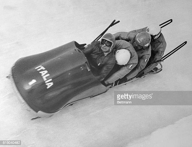 """Italy's four-man bobsled team flashes around a bend as they finish the second heat to win the event here. Italy's """"Flying Redhead,"""" Eugenio Monti,..."""