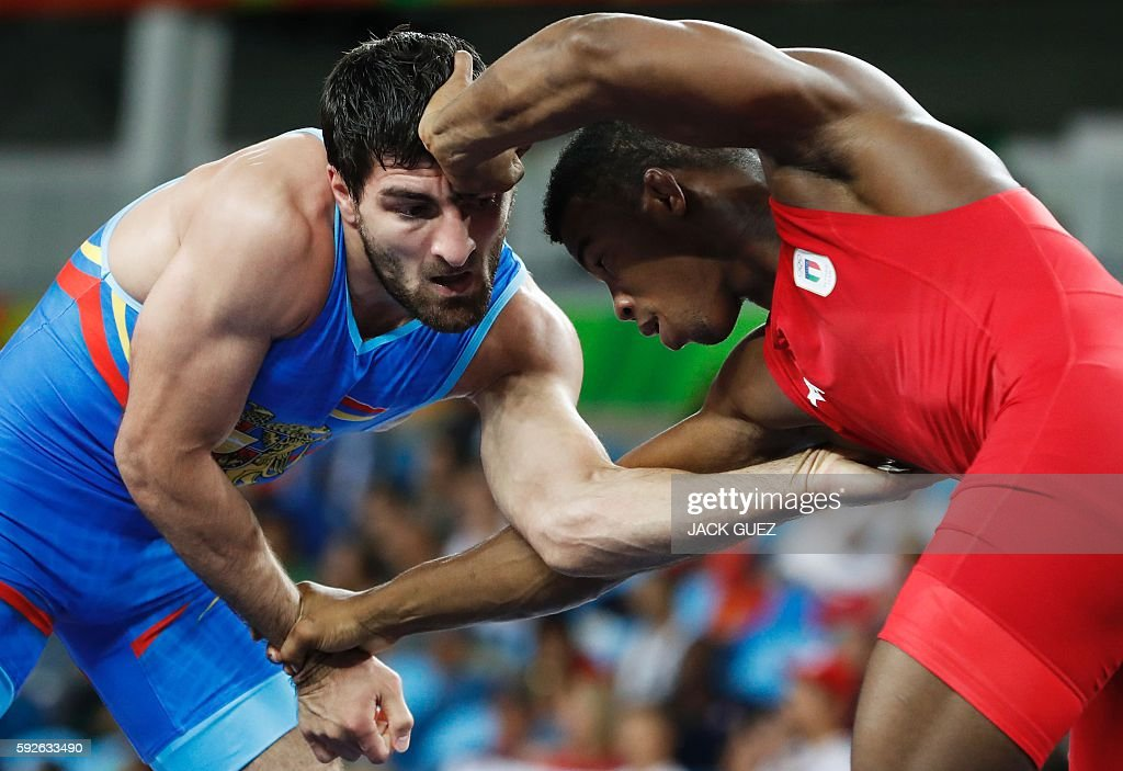 TOPSHOT - Italy's Frank Chamizo Marquez (red) wrestles with Armenia's Devid Safaryan in their men's 65kg freestyle round of 16 match on August 21, 2016, during the wrestling event of the Rio 2016 Olympic Games at the Carioca Arena 2 in Rio de Janeiro. / AFP / Jack GUEZ