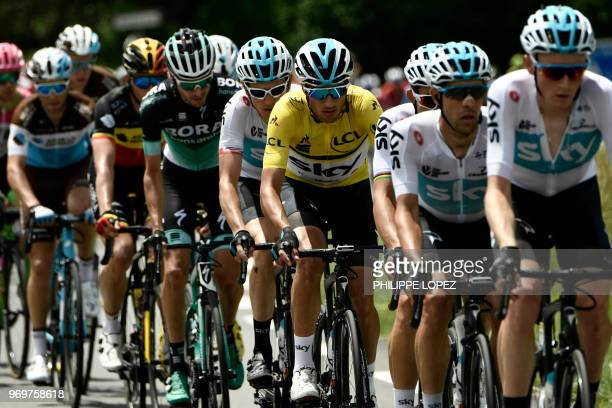 Italy's Gianni Moscon wearing the overall leader's yellow jersey rides at the lead of the pack with his Great Britain's Sky cycling team teammates...