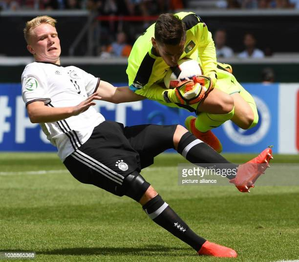 Italy's goalkeeper Alex Meret makes a save next to Germany's Phillipp Ochs during the UEFA European Under19 Championship group stage soccer match...