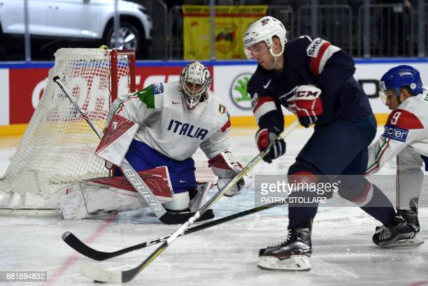 Italy´s goalkeeper Andreas Bernard and USA's JT Comper vie for the puck during IIHF Icehockey world championship first round match between USA and...