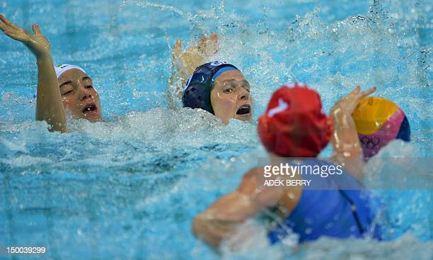 Italy's goalkeeper Elena Gigli reaches for the ball as Fran Leighton of Britain is challenged by Italy's Roberta Bianconi during the women's water...
