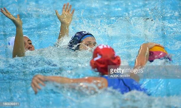Italy's goalkeeper Elena Gigli reaches the ball as Fran Leighton of Britain is challenged by Italy's Roberta Bianconi during the women's water polo...