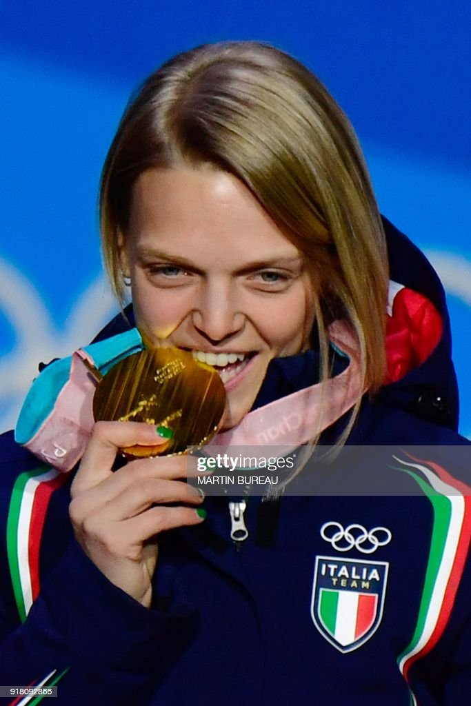 Italy's gold medallist Arianna Fontana bites her medal on the podium during the medal ceremony for the women's 500m short track at the Pyeongchang Medals Plaza during the Pyeongchang 2018 Winter Olympic Games in Pyeongchang on February 14, 2018. / AFP PHOTO / Martin BUREAU