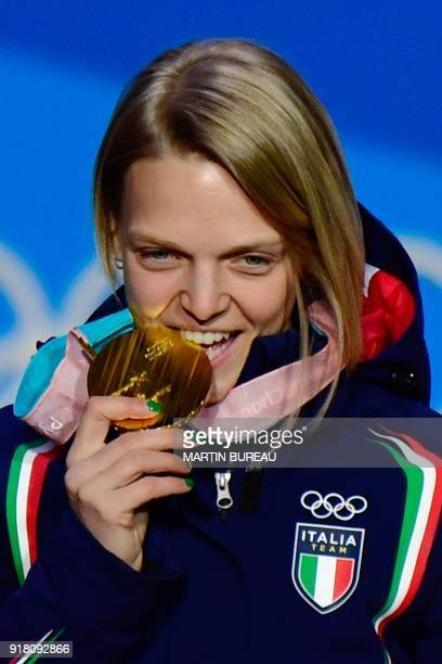 Italy's gold medallist Arianna Fontana bites her medal on the podium during the medal ceremony for the women's 500m short track at the Pyeongchang...