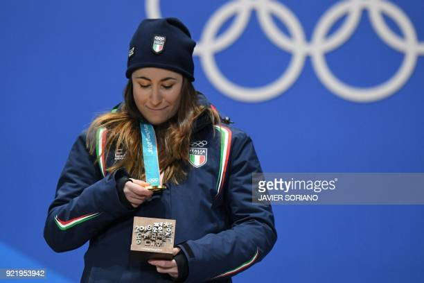 Italy's gold medallist Sofia Goggia looks at her medal on the podium during the medal ceremony for the alpine skiing Women's Downhill at the...