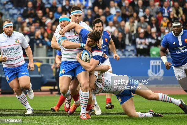 Italy's hooker Leonardo Ghiraldini tackles France's wing Damian Penaud during the Six Nations international rugby union match Italy vs France on...