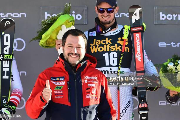 Italys Interior Minister and deputy PM Matteo Salvini joins winner Italy's Dominik Paris as he celebrates on the podium after the FIS Alpine World...