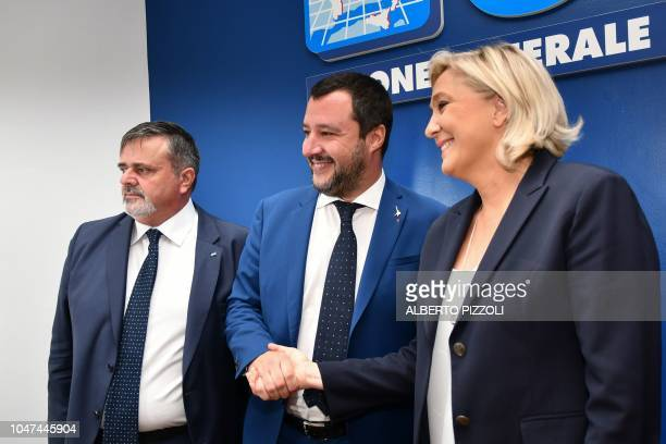 Italy's Interior Minister Matteo Salvini shakes hand with leader of France's farright National Rally party Marine Le Pen as general secretary of the...