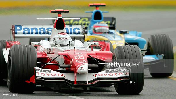 Italy's Jarno Trulli in a Toyota attempts to hold off the challenge of Spain's Fernando Alonso in a Renault before Trulli finishes in ninth place in...