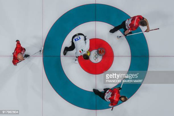 Italy's Joel Retornaz follows his stone next to opponents Canada's players Marc Kennedy Kevin Koe and Brent Laing during the curling men's round...