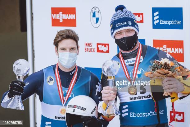 Italy's Kevin Fischnaller and Germany's Felix Loch celebrate as they share the winner trophy for men's sprint singles competition of of the Luge...