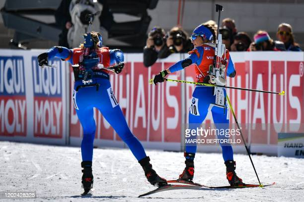 Italy's Lisa Vittozzi passes a relay to Italy's Dorothea Wierer during the Women 4x6 km Relay Competition at the IBU Biathlon World Cup in...